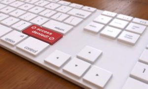 computer keyboard with red button that says access denied