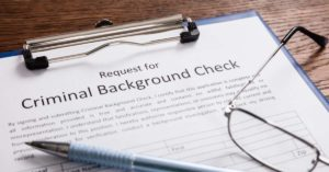 criminal background check form with pen and glasses on top