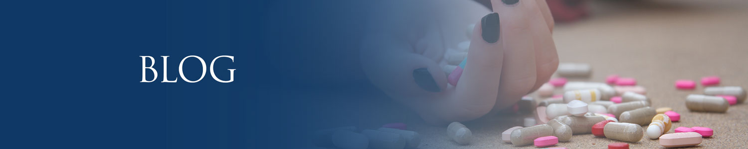 Hand on the ground with pills in and around it